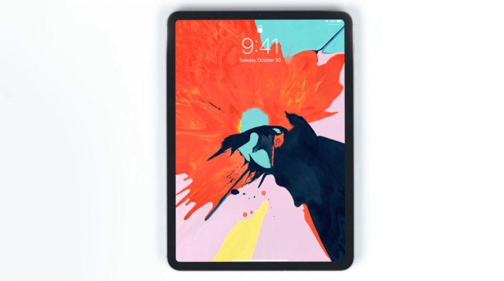 iPadPro2018が縦向きで中央にあり、オレンジと水色と黒が飛びちり合わさった壁紙になっている