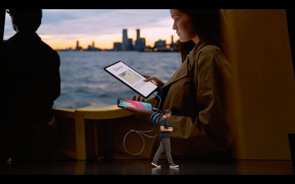 女性が右手で持ったipadproで左手に持ったiphonexsをusb-cで充電している様子